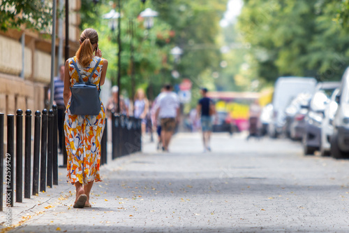 Fotografia A woman walking across a street and cars parked near curb on the side of the street on a parking lot