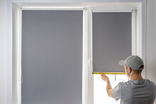 Man Installing Gray Roller Blinds On The Window