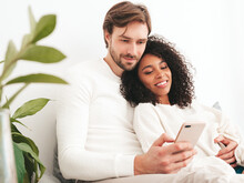 Smiling Beautiful Woman And Her Handsome Boyfriend. Happy Cheerful Multiracial Family. Multiethnic Models Lying In Bed And Hugging In White Interior.Looking At Cellphone Screen. Using Smartphone Apps