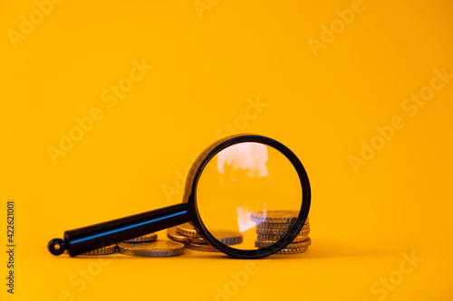 View of the coins through a magnifying glass. Increase in money, financial growth. On a yellow background.