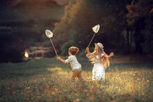 Beautiful Girl And Boy Are Catching Butterflies With Their Butterfly Net In Summer Park. Image With Selective Focus And Toning