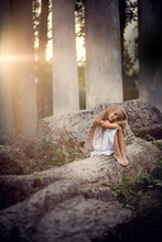 Portrait Of Beautiful Blonde Long-haired Girl Sitting On The Ruined Stones During The Sunset In Pavlovsk Park, Russia. Image With Selective Focus And Toning