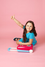 Full-length Portrait Of A Girl In A Blue Dress Sitting On The Floor With Her Hands On A Plastic Crimson Suitcase And Giving A Thumbs Up On Her Outstretched Arm, Isolated On A Pink Background.