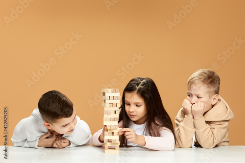 Obraz children plays with wooden constructor on desk. - fototapety do salonu