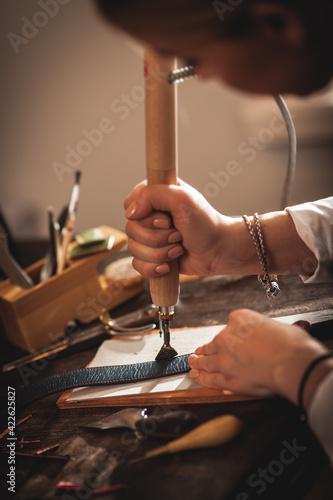 Obraz Leather handbag craftsman at work in a vintage workshop. Small business concept - fototapety do salonu
