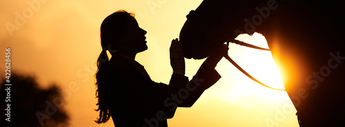 Fototapeta A horse rider girl stroking the head of a horse in the rays of the setting sun. Silhouette of a girl and a horse  obraz