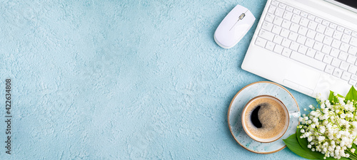 Fototapeta Home office desk table with coffee cup, bouquet of spring flowers lily of the valley flat lay. Workplace with laptop and coffee on blue background. Blogging, freelance, florist concept. Сopy space obraz