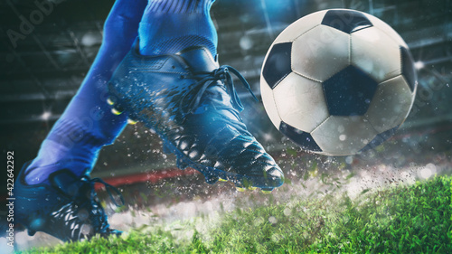 Photographie Football scene at night match with close up of a soccer shoe hitting the ball wi