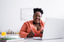 Cheerful African American Plus Size Woman Holding Pen And Looking At Laptop