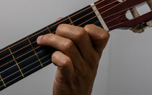 Hands Of A Dark Man On The Six Strings Of A Black Guitar Neck Composing The C Note With A White Background. It Refers To Fun At Home, Music Band, Composition And Entertainment.