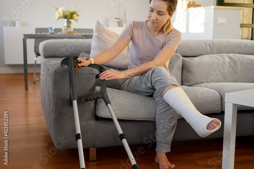 Fotografia Woman in her late twenties on couch at home with elbow crutches and orthopedic plaster
