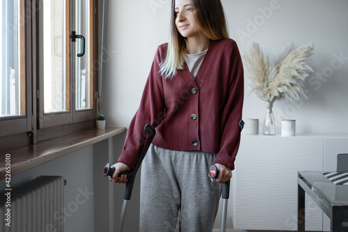 Canvas Adult woman in her late twenties on crutches at home is looking into the window with hope