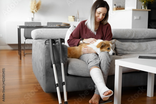 Adult woman in her late twenties on couch at home with crutches and orthopedic plaster caress the dog Fotobehang