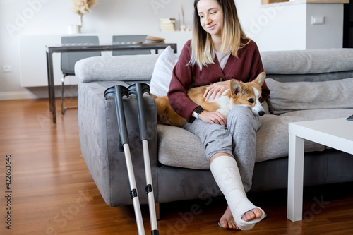 Adult woman in her late twenties on couch at home with crutches and orthopedic plaster caress the dog Poster Mural XXL