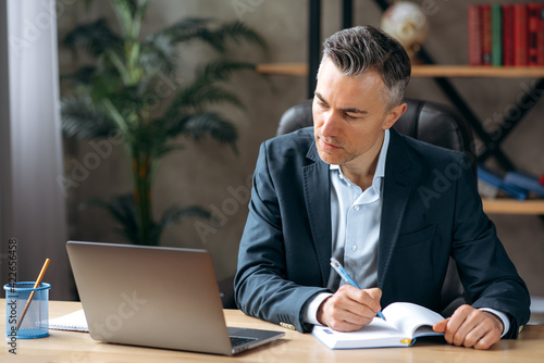 Successful serious adult attractive caucasian business leader or ceo, sitting at workplace in the office in a formal suit, concentrated working in a laptop, browsing internet, analyzes information