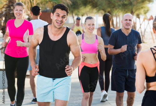 Photo People leading healthy lifestyle, jogging during outdoor workout on city seafron