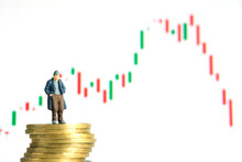 Miniature Tiny People Toys Photography. People Standing Above Coin Stack Does Not Have Money Or Bankrupt, Stock Market Candle Chart Fell Down, Isolated On White Backgrounds.
