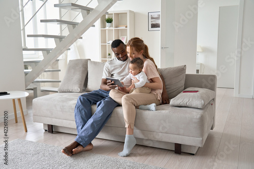 Fototapeta Happy young multi ethnic diverse parents having fun using digital tablet computer holding cute little mixed race baby child daughter sitting on couch in modern cozy living room at home together. obraz