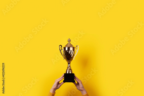 Fotografiet woman holding up a gold trophy cup as a winner in a competition