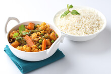 MIX VEGETABLE CURRY WITH RICE - Indian Recipe, Mixed Veg Containing Carrots, Cauliflower, Green Peas And Beans With Traditional Masala And Curry, Red Hot And Spicy Served In A Ceramic Bowl