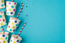 Top View Photo Of Birthday Party Composition Sequins And Polka Dots Paper Cups With Striped Straws On The Left On Isolated Blue Background With Copyspace On The Right