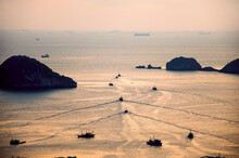 Silhouettes Of Fishermen Boats Sail Away To The Open Sea To Catch And Bring Fresh Fish At Cat Ba Island During Beautiful Sunset, Halong Bay, Vietnam