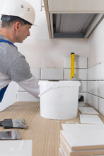 The Tile Installation Wizard Measures The Correct Laying Of White Tiles, Using The Yellow Level