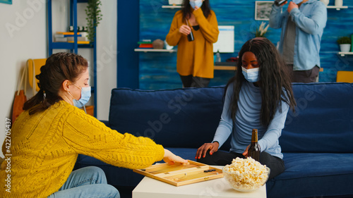 Canvas Multiethnical women playing backgammon wearing face mask as prevention for covid 19 spread during global pandemic sitting on sofa drinking beer and eating popcorn