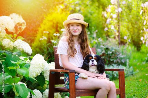 happy kid girl relaxing in summer garden with her cavalier king charles spaniel Fototapet