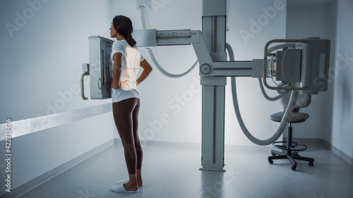 Hospital Radiology Room: Beautiful Multiethnic Woman Standing in the X-Ray Machine. Adult Female Undergoes Medical Exam and is Scanning Chest, Back, Heart, Lungs in Modern Clinic Office.