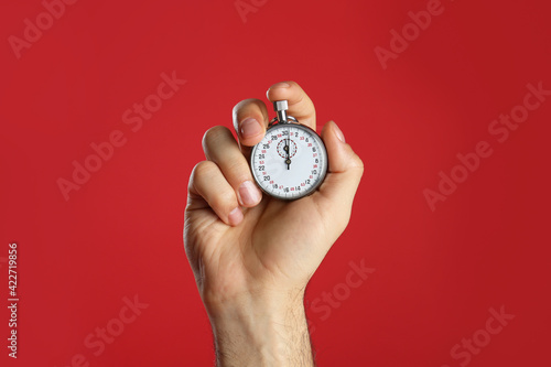 Wallpaper Mural Man holding vintage timer on red background, closeup