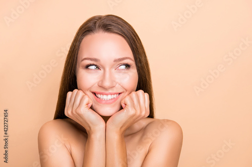 Fototapeta Portrait of pretty curious cheerful girl pure soft skin looking aside copy space isolated over beige pastel color background obraz