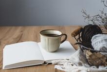 Eine Rustikale Kaffeetasse Auf Einem Offenen Buch Und Strickzeug In Einem Korb Auf Einem Braunen Holztisch. Vitage Stil, Hygge.