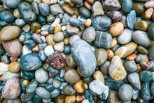 Colored Stones On The Beach Soaked By The Textura Water.
