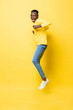 Young cheerful excited African man jumping with clenching hands on isolated yellow studio background
