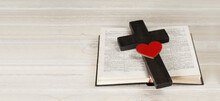 Open Book Holy Bible. Wooden Cross Of Jesus. Red Heart Love. On A Wooden White Background. Death Symbol. Religious Christian