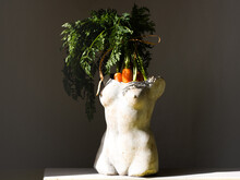 A Vase Of The Shape Of A Female Torso Stands On The Table In It A Young Carrot With Tops. Seasonal Vegetables Concept, Still Life