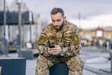 A Military Soldier Sits On A Bench At A Bus Stop Waiting For A B