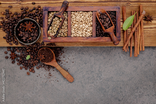 Fototapeta Various of roasted coffee beans in wooden box with manual coffee grinder setup on shabby wooden background. obraz