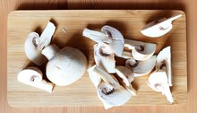 Whole Sliced And Chopped White Button Mushrooms On A Wooden Chopping Board.