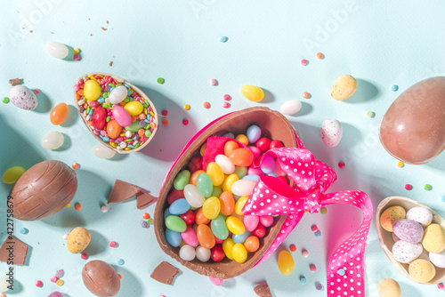 Fototapeta Various Easter Colorful Sweets and Chocolate Eggs flatlay on light blue background top view copy space obraz