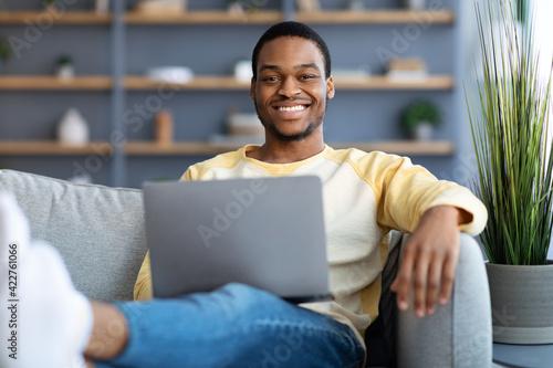 Fototapeta Positive black man chilling on sofa, using laptop obraz