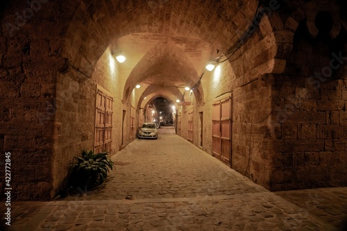 Tablou Canvas arcade passage at the old center of the Lebanese city Batroun with parked cars a