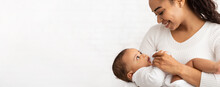 African Mother Feeding Baby Standing On White Background, Panorama, Cropped