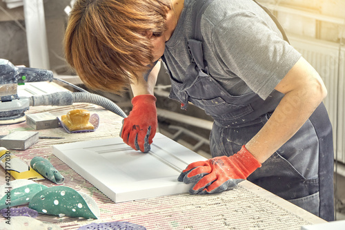 Fotografia Female employee in dirty uniform and working gloves polishes wooden part of furn