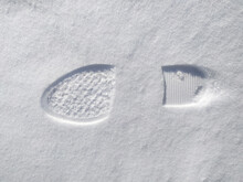 Footprints Of A Woman's Boot In The Snow. A Clear Imprint Of The Pattern Of The Sole Of The Boots On A Snowy Field.