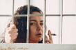 Leinwandbild Motiv Young brunette curly woman in orange suit behind jail bars smokes marijuana joint. Female in colorful overalls portrait.