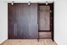 Open Doors Of Elegant Wardrobe With Inner Drawer Made Of Dark Oak Veneer With Shiny Metal Handles In Minimal Style In Room