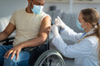 Covid-19 vaccination for homebound people. Doctor giving coronavirus vaccine to handicapped male patient in wheelchair