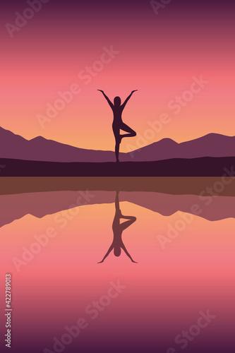 Fototapeta premium girl makes yoga by the lake at sunset